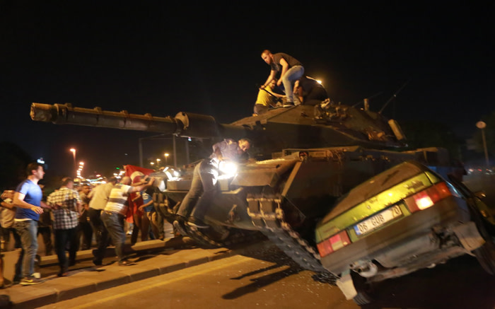 A tank crashes against a car as people take to the streets in Ankara, Turkey, during a protest against military coup. Picture: AFP.