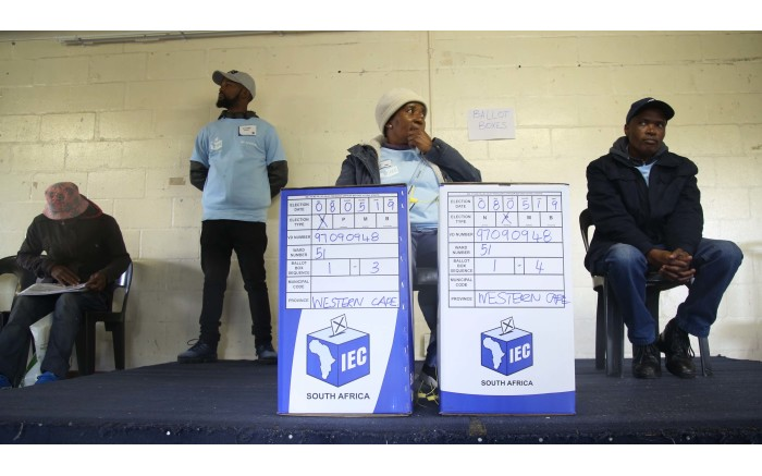 An IEC official sits behind two ballot boxes, as she waits for voters. Picture: Bertram Malgas