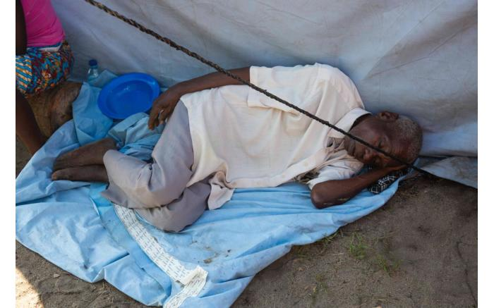 A man sleeps next to a tent in a relief camp set up for people displaced by Cyclone Idai. Christa Eybers/EWN