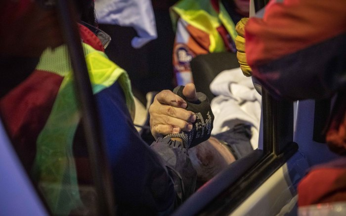 A victim of a motor vehicle accident grips the hand of a medic from ER24 along the N1 outside Fourways. Picture: Thomas Holder/EWN