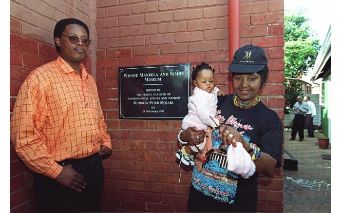 Winnie Madikizela-Mandela, her son-in-law Zweli Hlongwane and her great granddaughter Zenani pose at the Mandela's home in Soweto.