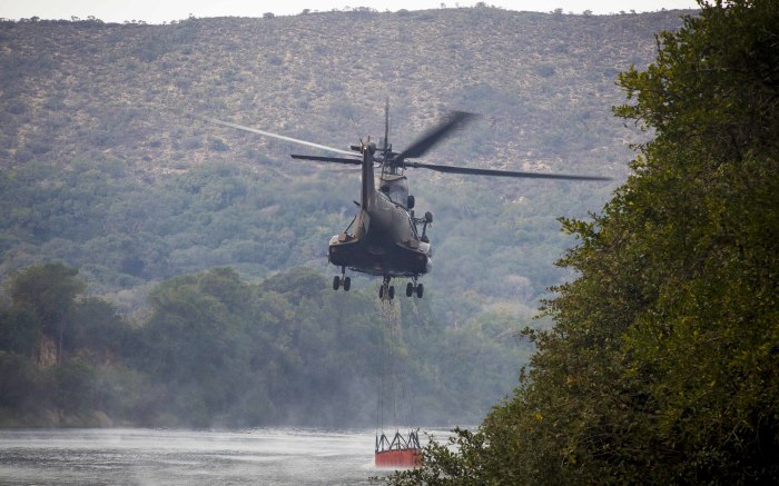An SA Airforce Oryx picks up water from a farm river to bomb nearby fires.