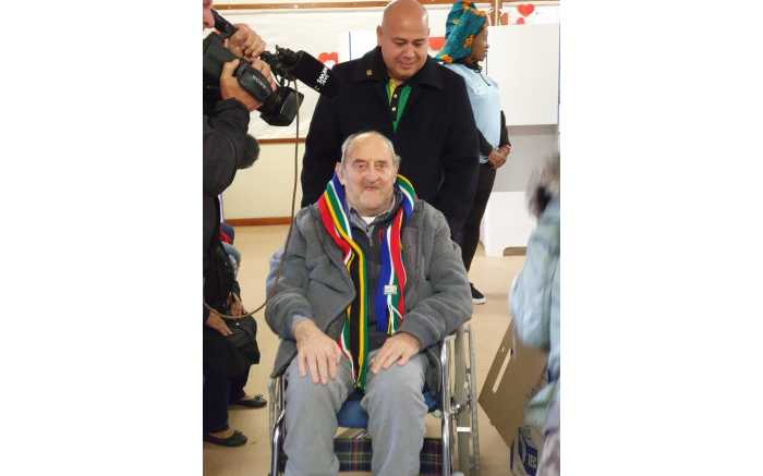 Isithwalandwe Dennis Goldberg voting in Hout Bay assisted by ANC Western Cape secretary Faiez Jacobs.