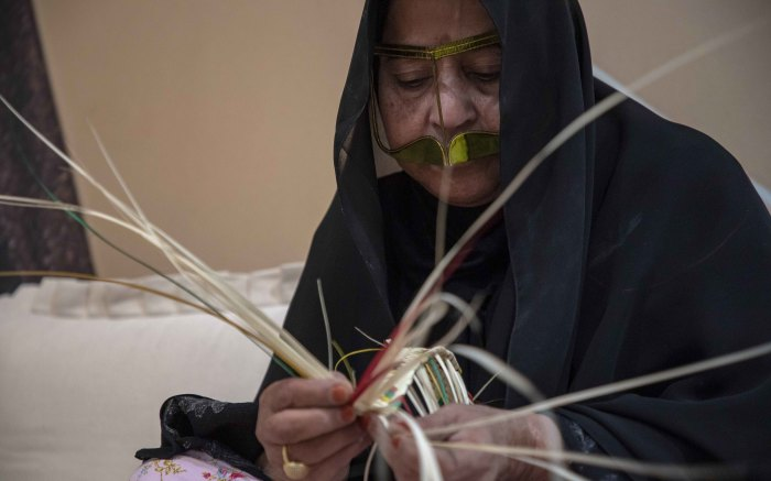A traditional weaver at the heritage centre in Abu Dhabi weaves together a strap for a bag she is creating. Picture: Thomas Holder/EWN