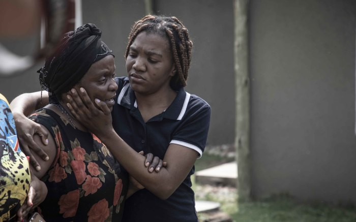 Enock's mother, Antionette Mpianzi, is comforted as she becomes emotional.