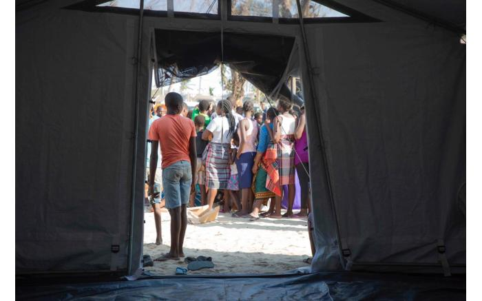 People wait in line for food at a relief camp set up for victims of Cyclone Idai who have fled to Beira . Christa Eybers/EWN