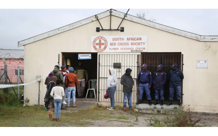 Police keep a close eye on voters as they queue up to make their mark in the 2019 Elections. Picture: Bertram Malgas