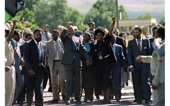 Nelson Mandela and his wife Winnie raise their fists and salute cheering crowds upon Mandela's release from the Victor Verster prison.