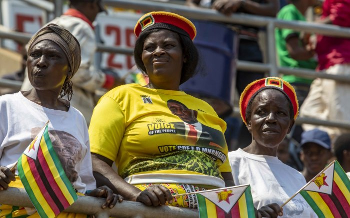 Supporters of the late Robert Mugabe wait in the stands during the funeral ceremony.