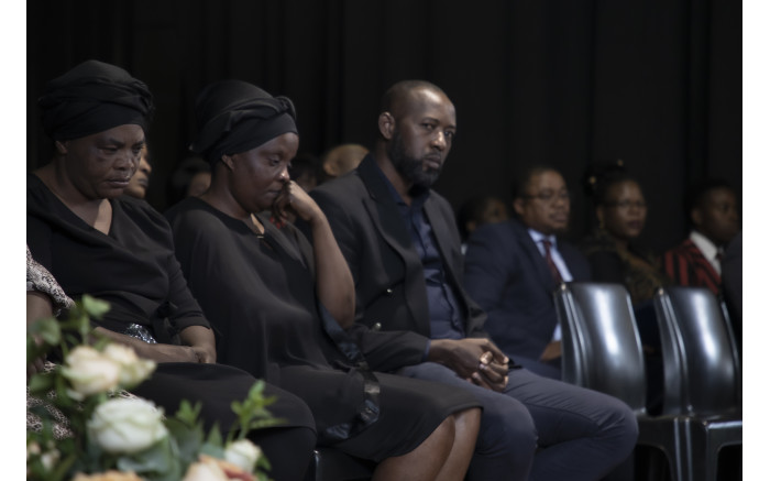 Enock Mpianzi's family sit quietly and sombre on stage. Picture: Xanderleigh Dookey