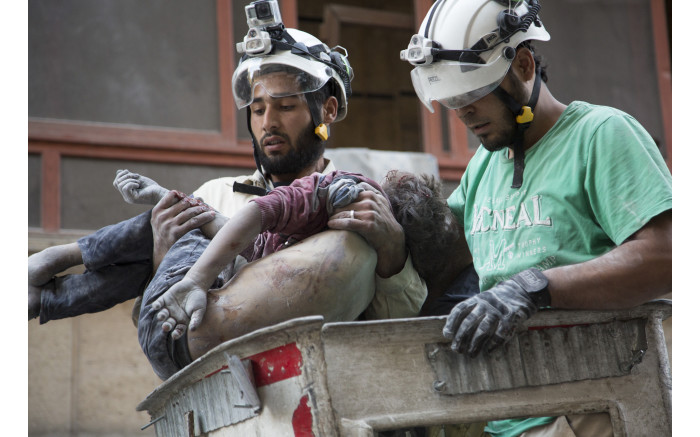 Syrian rescuers hold the body of a girl after pulling her from the rubble of a building. Picture: AFP.