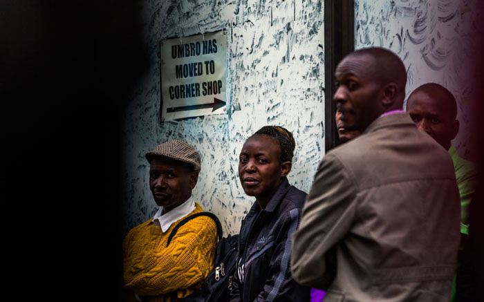 Harare residents look on as an armoured personnel carrier of the Zimbabwean military stands at an intersection. Picture: AFP.