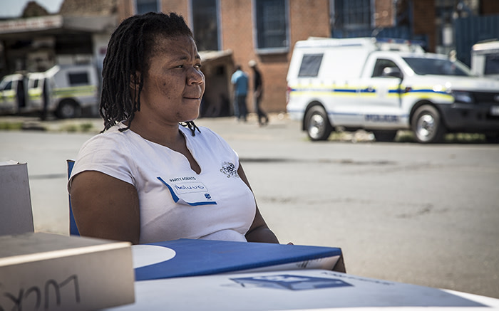 An IEC official sits at a temporary registration station in Denver as police watch over the area. Picture: Reinart Toerien/EWN