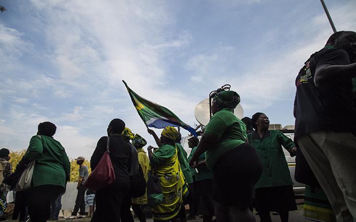 Members of the ANC women's league walk towards Winnie Madikizela-Mandela's home
