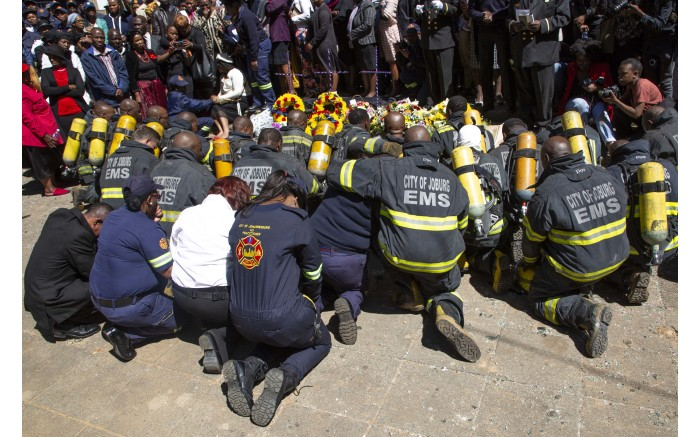 Firefighters who fought the blaze with those who died have a moment of silence at their memorial site.