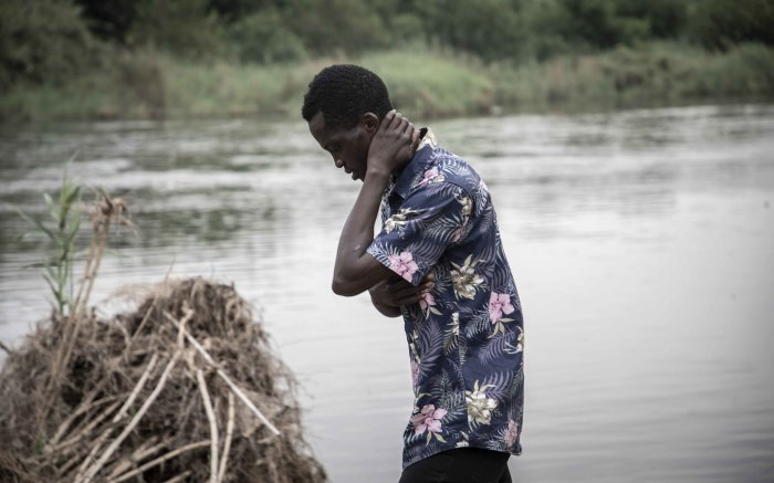 Kadilo stands on the banks of the river where Enock was washed away.