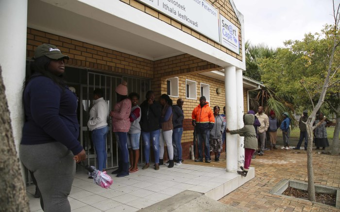 A small queue of voters stand outside the Hector Peterson Library in Lwandle waiting to vote. Picture: Cindy Archillies/EWN.