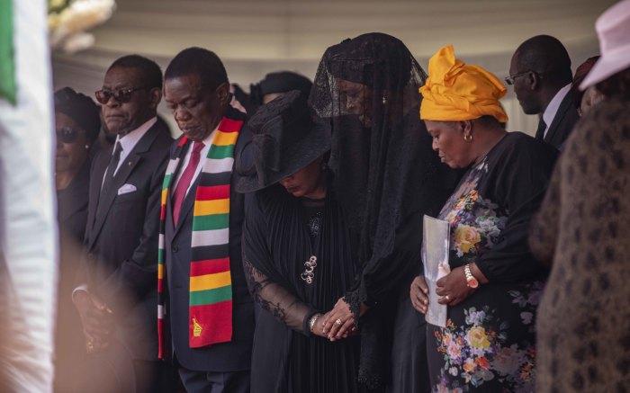 Zimbabwean first lady Auxillia Mnangagwa clasps the hand of former first lady Grace Mugabe during proceedings.