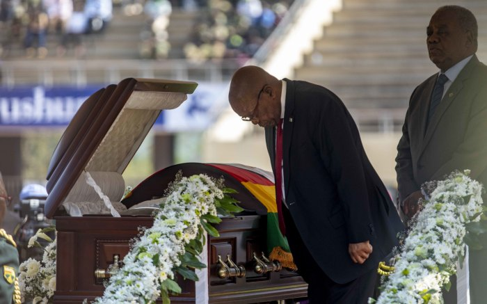 Former South African President Jacob Zuma bows to the late former President Robert Mugabe.