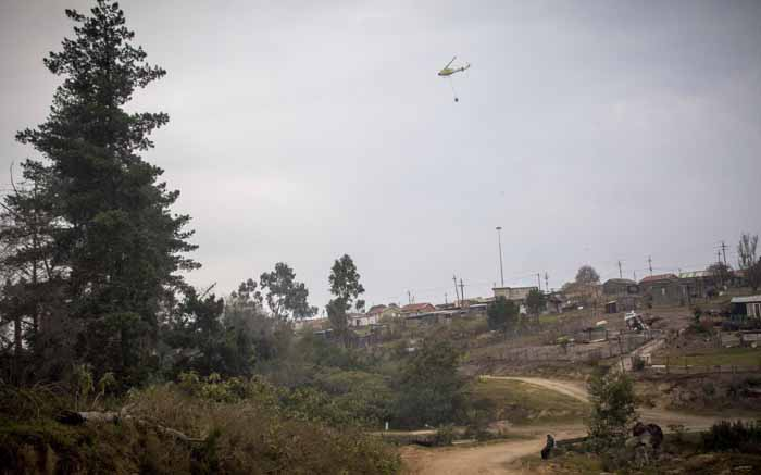 A water bombing helicopter flies over Concordia, an informal settlement in Knysna, before water bombing nearby areas.