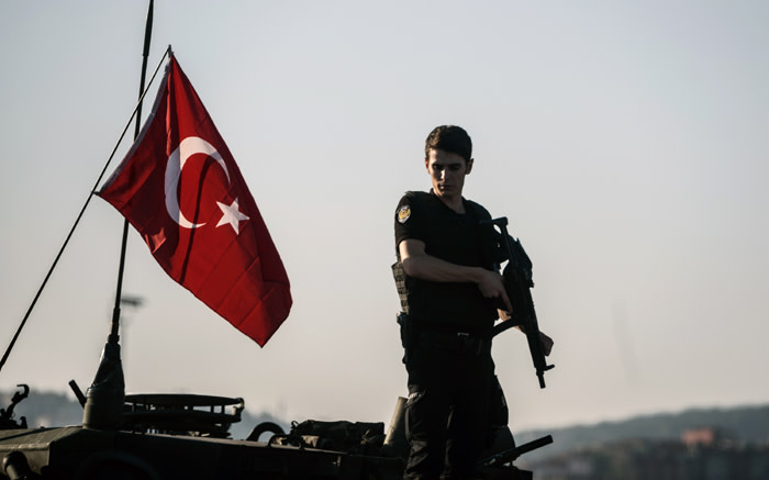An anti-riot police officer stands guard after a military position on the Bosphorus bridge was taken over in Turkey. Picture: AFP.