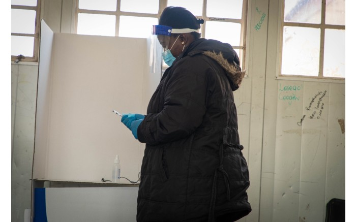 A voting official sanitises a pen as a COVID-19 regulation measure at Rantailane Secondary School, in Ga-Rankuwa.
