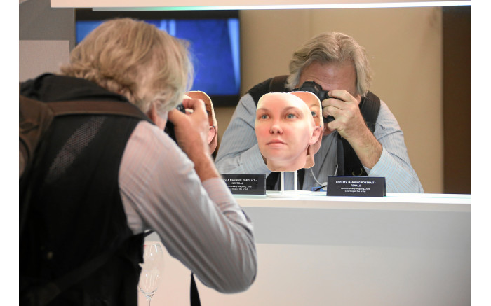 A man takes a picture of a mask of clones at the World Economic Forum's 2016 annual meeting. Picture: swiss-image.ch