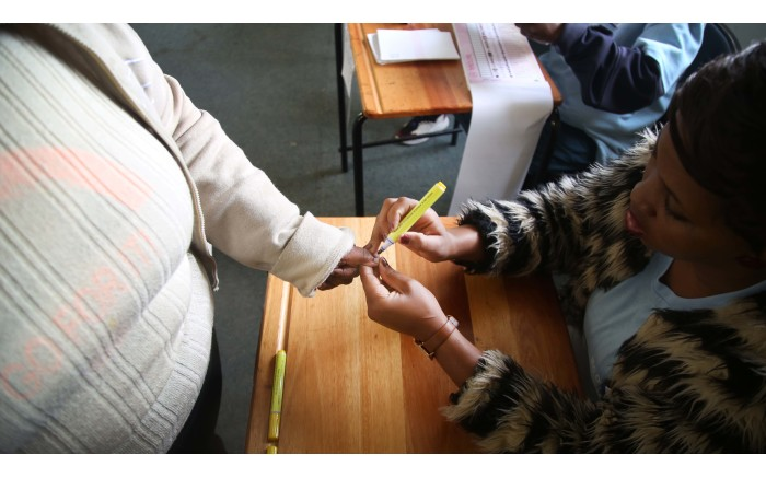 A Langa resident gets her thumb marked before casting her vote. Picture: Bertram Malgas