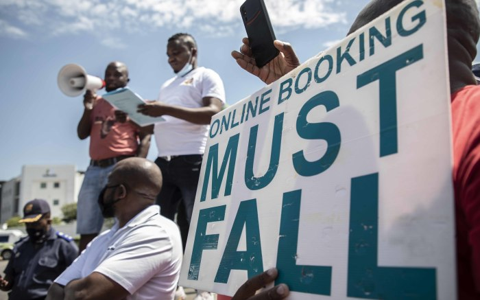 A protester holds up a placard as the police keep them from moving closer to the RTMC offices. Picture: Abigail Javier/EWN