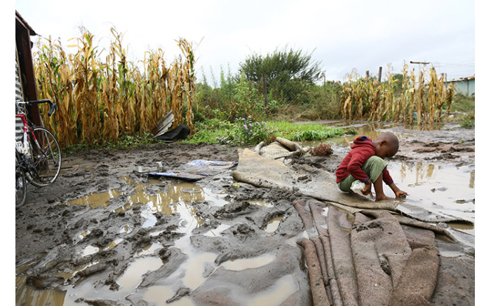 A child plays in a puddle of water after heavy rains flooded an informal settlement in Soshanguve, Pretoria. Picture: Sethembiso Zulu/EWN.