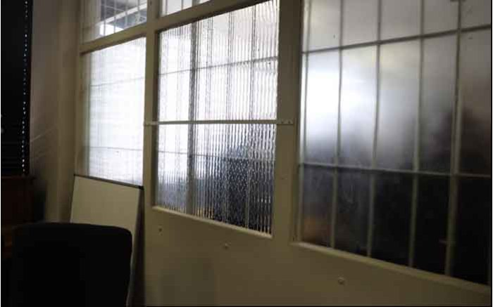 The wall and window separating interrogation rooms at the Johannesburg Central Police Station.