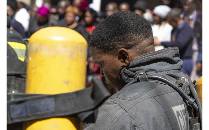 A firefighter stands in prayer at the site where his 3 colleagues died last week.
