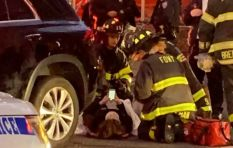 [VIDEO]  Bizarre moment as woman checks her phone while EMS lift car off her