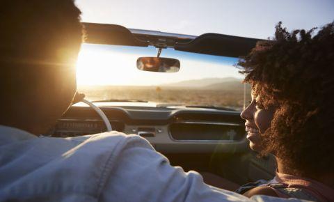 man-woman-couple-sit-in-car-road trip-convertible-sunset-views-summer-123rf