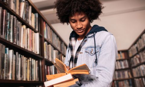 Young man reading books in library literature 123rflifestyle 123rf