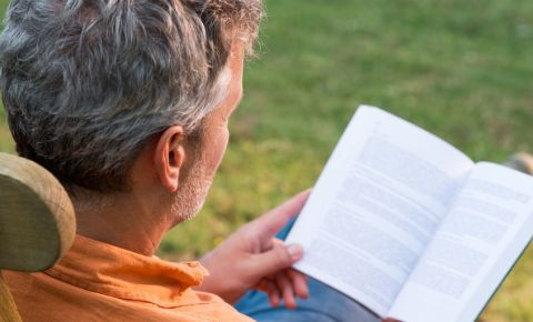 man-reading-book-grey-hair-outside-garden-123rf