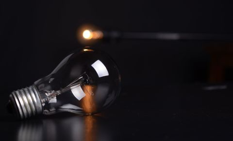 Light bulb against dark background, electricity, load shedding. Image: Pexels.